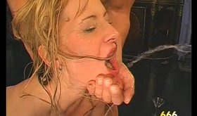Busty blonde is standing on her knees and drinking man's cum