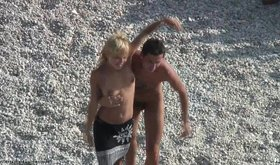 Horny half naked couple of lovers are seductively dancing on beach