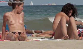 Two cute topless girls are having a conversation on the beach